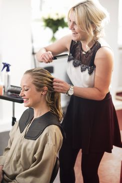 Hairdresser combing customer's hair