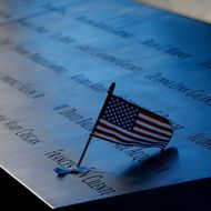 NEW YORK - SEPTEMBER 11:  An American flag is stuck in a plaque of names of the victims of the September 11 attacks at the North Pool memorial during observances for the eleventh anniversary of the terrorist attacks on lower Manhattan at the World Trade Center site September 11, 2012 in New York City. The nation is commemorating the eleventh anniversary of the September 11, 2001 attacks which resulted in the deaths of nearly 3,000 people after two hijacked planes crashed into the World Trade Center, one into the Pentagon in Arlington, Virginia and one crash landed in Shanksville, Pennsylvania. (Photo by Mike Segar-Pool/Getty Images)