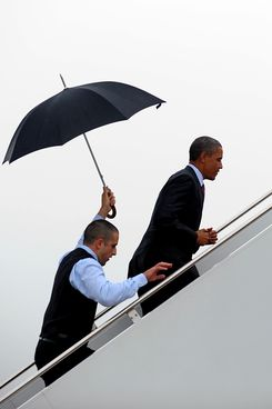 "Air Force One Staff Sergeant Brian Barnett (L) follows behind US President Barack Obama with an umbrella as he boards Air Force One at Andrews Air Force Base, Maryland, September 9, 2011. Obama was headed to Richmond, Virginia, where he will discuss what the White House described as ""bipartisan proposals to grow the economy and create jobs.""       AFP PHOTO/Jim WATSON (Photo credit should read JIM WATSON/AFP/Getty Images)"