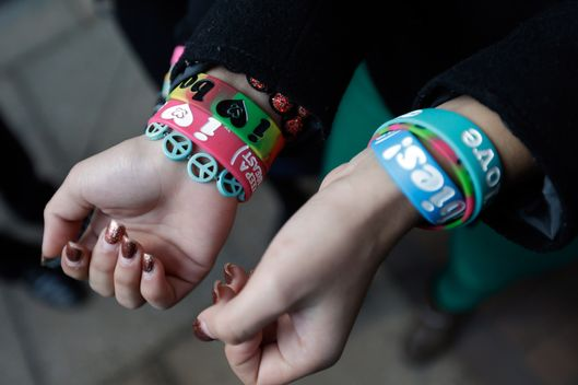 "In this Feb. 20, 2013 file photo, Easton Area School District students Brianna Hawk, 15, left, and Kayla Martinez, 14, display their  ""I (heart) Boobies!"" bracelets for photographers outside the U.S. Courthouse in Philadelphia. The Easton Area School District says it will take its fight against ""I (heart) Boobies!"" bracelets to the U.S. Supreme Court. The board voted 7-1 Tuesday night, Oct. 29, 2013 to appeal a decision rejecting its claim the bracelets are lewd and should be banned from school. The bracelets are designed to promote breast cancer awareness among young people."
