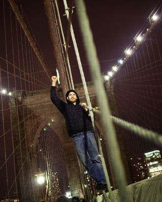 NEW YORK, NY - NOVEMBER 17: A protestor affiliated with the Occupy Wall Street Movement raises his fist in the air while chanting on the Brooklyn Bridge in New York City on November 17, 2011. The day has been marked by sporadic violence, arrests, and injuries sustained by both protestors and police. Protestors marched around Wall Street throughout the morning, attempting to disrupt businesses from operating. (Photo by Andrew Burton/Getty Images)