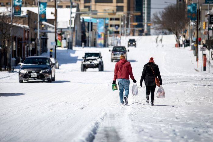 People carrying groceries up a snowy hill in Austin.