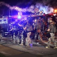 FERGUSON, MO - AUGUST 17:  Police advance while sending a volley of tear gas toward demonstrators protesting the killing of teenager Michael Brown on August 17, 2014 in Ferguson, Missouri. Police shot smoke and tear gas into the crowd of several hundred as they advanced near the police command center which has been set up in a shopping mall parking lot. Brown was shot and killed by a Ferguson police officer on August 9. Despite the Brown family's continued call for peaceful demonstrations, violent protests have erupted nearly every night in Ferguson since his death.  (Photo by Scott Olson/Getty Images)