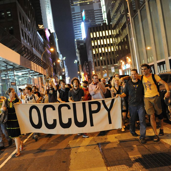 New york, United States. 30th May 2012 -- Protesters carry a large 'Occupy' banner as they march in the streets. -- Occupy Wall Street has a march in New York in solidarity with the Quebec students striking over student fees and Bill 78, which effectively outlaws most protests, who use kitchen pots and pans as their symbol.