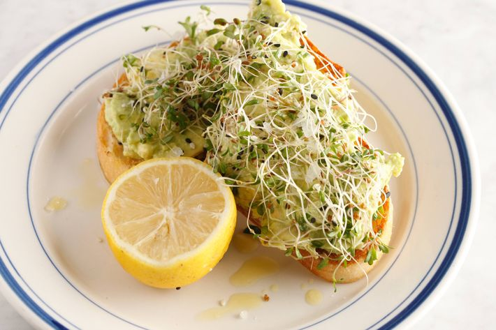 Avocado toast with alfalfa sprouts, toasted sesame seeds, and pickled shallots.