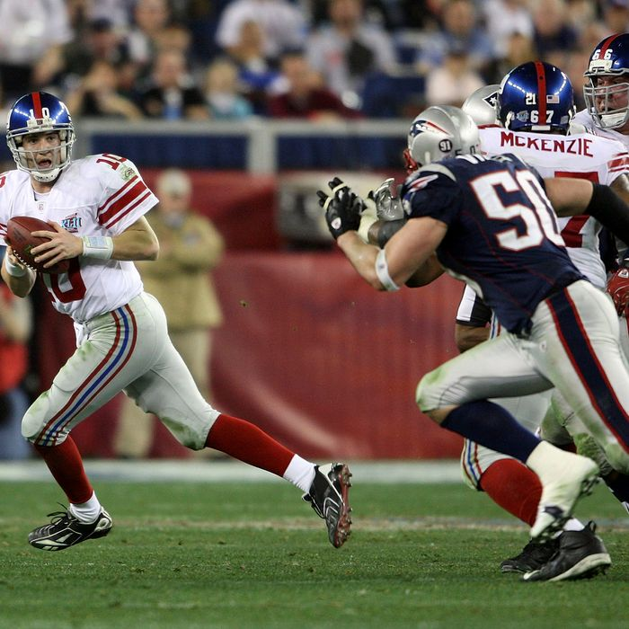 GLENDALE, AZ - FEBRUARY 03: Eli Manning #10 of the New York Giants scrambles away from th New England Patriots defense to throw a 32 yard pass to David Tyree #85 of the Giants during the four quarter of Super Bowl XLII on February 3, 2008 at the University of Phoenix Stadium in Glendale, Arizona. (Photo by Andy Lyons/Getty Images)
