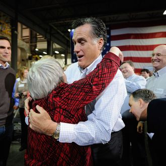 CEDAR RAPIDS, IA - DECEMBER 09: Republican presidential hopeful and former Massachusetts Gov. Mitt Romney (R) hugs supporter Joni Scotter, from Marion, Iowa, as his son Josh Romney (L) looks on at a town hall meeting at Diamond V South Plant on December 9, 2011 in Cedar Rapids, Iowa. Romney is campaigning in the state one month before the Iowa caucuses and one day before the GOP presidential debate. (Photo by Kevork Djansezian/Getty Images)
