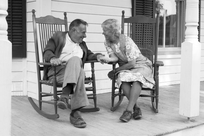 1970s elderly couple in rocking chairs on porch holding hands
