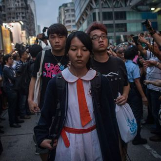 HONG KONG - OCTOBER 03: Students and pro-democracy activists leave the protest site as local police hold back local residents and pro-government supporters on October 3, 2014 in Mong Kok, Hong Kong. Fights broke out between local residents and pro government supporters when they attempted to force pro-democracy activists from their protest site. Thousands of pro democracy supporters continue to occupy the streets surrounding Hong Kong's Financial district. Protest leaders have set an October 1st deadline for their demands to be met and are calling for open elections and the resignation of Hong Kong's Chief Executive Leung Chun-ying. (Photo by Chris McGrath/Getty Images)