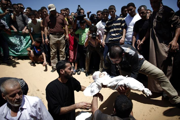 Relatives of seven-month-old Ali Deif, the son of Hamas's military commander Mohammed Deif, place his body into a grave during his funeral at the Beit Lahia cemetery in the northern Gaza Strip on August 20, 2014. Several thousand mourners joined the funeral procession for the wife and baby son of Hamas's military commander, angrily demanding revenge against Israel.
