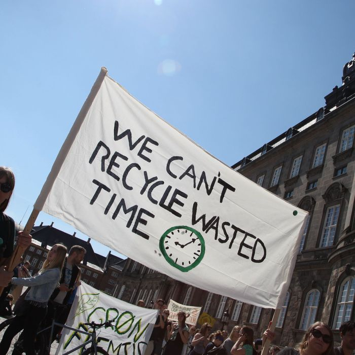 """Denmark, Copenhagen: Two demonstrators hold a banner with the inscription """"We Can't Recycle Wasted Time"""" in front of the Danish Parliament during a climate protest."""