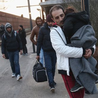 Migrants, many of them from Syria, walk to police vans after police found them while checking the identity papers of passengers on a train arriving from Germany on January 6, 2016 in Padborg, Denmark.