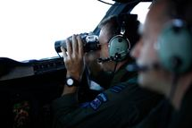 IN FLIGHT - MARCH 29: Wing Commander Rob Shearer looks through binoculars on the flight deck of a Royal New Zealand Air Force P-3K2 Orion aircraft searching for missing Malaysian Airlines flight MH370 on March 29, 2014 over the southern Indian Ocean. Chinese ships trawled a new area in the Indian Ocean for a missing Malaysian passenger jet on Saturday, as the search for Flight MH370 entered its fourth week amid a series of false dawns over sightings of debris. The Malaysian airliner disappeared on March 8 with 239 passengers and crew on board and is suspected to have crashed into the southern Indian Ocean.   (Photo by Jason Reed-Pool/Getty Images)
