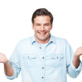 A smiling man gesturing with his palms up while isolated on a white background