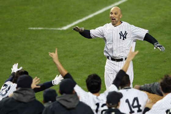 Raul Ibanez #27 of the New York Yankees reaches his teammates at home place after hitting a walk off home run in the bottom of the twelfth inning against the Baltimore Orioles  in Game Three of the American League Division Series at Yankee Stadium on October 10, 2012 in the Bronx borough of New York City.