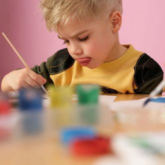 Little boy painting, sticking his tongue out