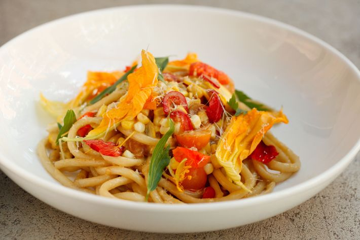 Bucatini pasta with fresh corn, squash blossoms, and spring onions.