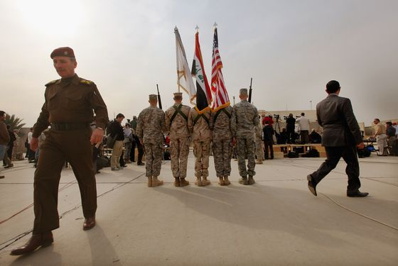 BAGHDAD, IRAQ - DECEMBER 15:  U.S. Military personnel holding the US flag, Iraq flag, and the US Forces Iraq colors stand as an Iraqi Army officer (L) walks past before the start of a casing ceremony where the United States Forces- Iraq flag was retired, signifying the departure of United States troops from Iraq, at the former Sather Air Base on December 15, 2011 in Baghdad, Iraq. United States forces are scheduled to entirely depart Iraq by December 31, there are currently around 4,000 troops remaining in Iraq.(Photo by Mario Tama/Getty Images)