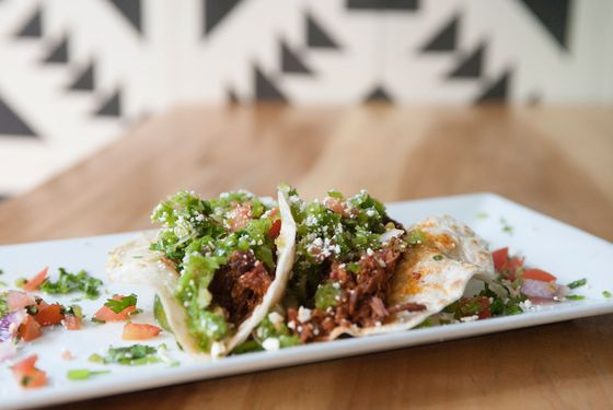 Javelina's Lamb Tacos - slow-roasted lamb, cooked barbacoa style, red chile sauce, salsa verde cruda, and cotija cheese.