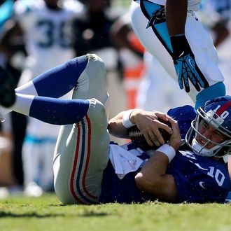 CHARLOTTE, NC - SEPTEMBER 22: Eli Manning #10 of the New York Giants is knocked to the ground during their game against the Carolina Panthers at Bank of America Stadium on September 22, 2013 in Charlotte, North Carolina. (Photo by Streeter Lecka/Getty Images)
