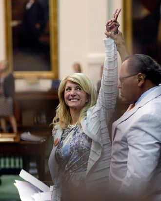 Sen. Wendy Davis, D-Fort Worth, left, who tries to filibuster an abortion bill, reacts as time expires, Tuesday, June 26, 2013, in Austin, Texas. Amid the deafening roar of abortion rights supporters, Texas Republicans huddled around the Senate podium to pass new abortion restrictions, but whether the vote was cast before or after midnight is in dispute. If signed into law, the measures would close almost every abortion clinic in Texas. (AP Photo/Eric Gay)