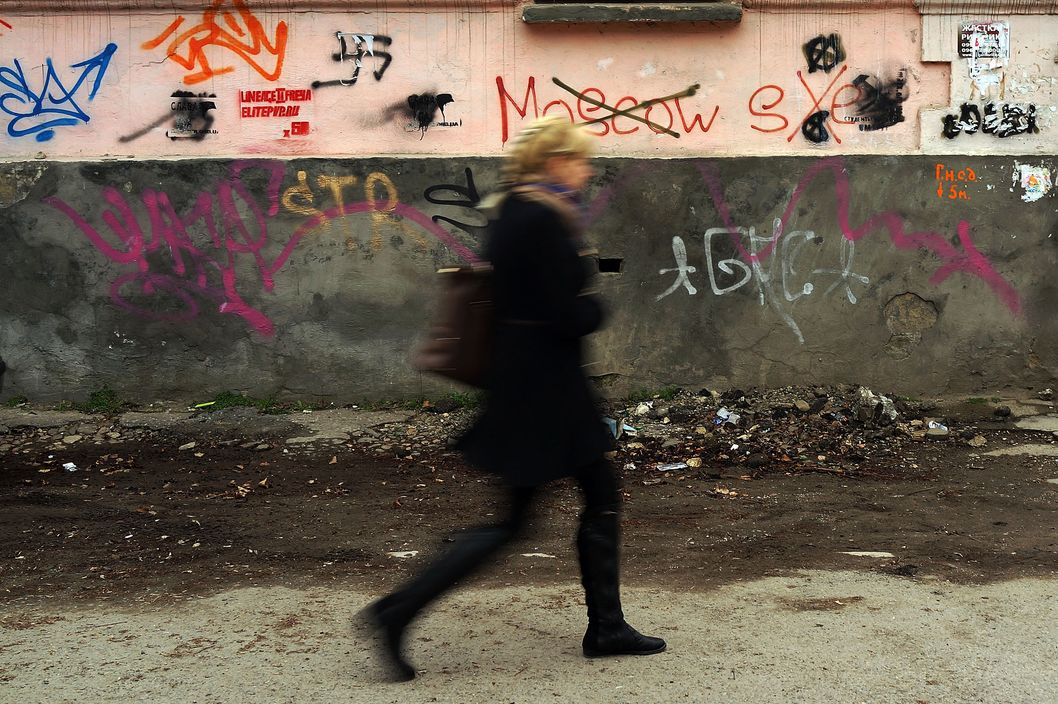 SIMFEROPOL, UKRAINE - MARCH 17: A woman walks by grafitti on a wall on March 17, 2014 in Simferopol, Ukraine. Voters on the autonomous Ukrainian peninsular of Crimea voted overwhelmingly yesterday to secede from their country and join Russia. Crimea will seek to adopt the Russian Ruble as its official currency. (Photo by Spencer Platt/Getty Images)
