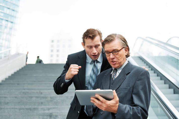 Businessmen looking at digital tablet