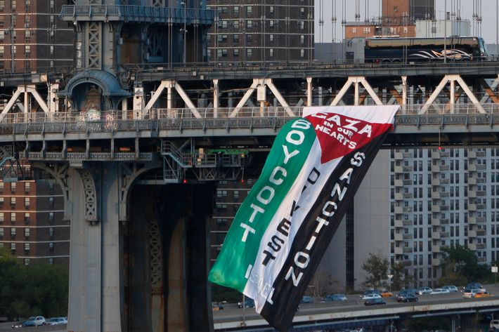 Demonstrators hang a protest flag from the south side of the Manhattan Bridge as a pro-Palestinian rally (not pictured) makes its way across the nearby Brooklyn Bridge, Wednesday, Aug. 20, 2014, in New York. (AP Photo/Jason DeCrow)