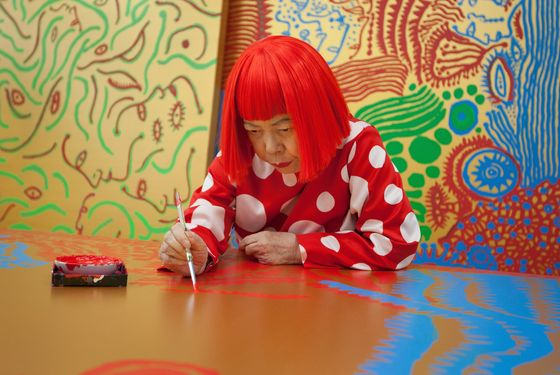 TOKYO, JAPAN - JANUARY 25:  Japanese artist Yayoi Kusama sits working on a new painting, in front of other newly finished paintings in her studio, on January 25, 2012 in Tokyo, Japan. Yayoi Kusama, who suffers from mental health problems and lives in a hospital near her studio, is one of today's most highly revered and popular of Japanese artists. She is one of the world's top selling living female artists breaking records in the millions. A major retrospective of her work is on display at Tate Modern in London through June 5, 2012.  (Photo by Jeremy Sutton-Hibbert/Getty Images)