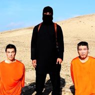 A video released by ISIS on social media Tuesday, Jan. 20, 2015, purportedly shows a masked man standing over two kneeling men in orange jumpsuits. The terror groups threatened to kill the two Japanese hostages unless Tokyo pays $200 million.