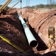 A sixty-foot section of pipe is lowered into a trench during construction of the Gulf Coast Project pipeline in Prague, Oklahoma, U.S., on Monday, March 11, 2013. The Gulf Coast Project, a 485-mile crude oil pipeline being constructed by TransCanada Corp., is part of the Keystone XL Pipeline Project and will run from Cushing, Oklahoma to Nederland, Texas.