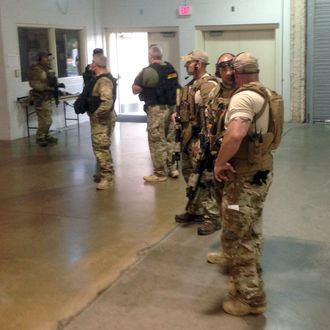 Members of the Garland Police Department are stand inside the Curtis Culwell Center on Sunday, May 3, 2015, in Garland, Texas. A contest for cartoons depictions of the Prophet Muhammad in the Dallas suburb is on lockdown Sunday after authorities reported a shooting outside the building. (AP Photo Nomaan Merchant)