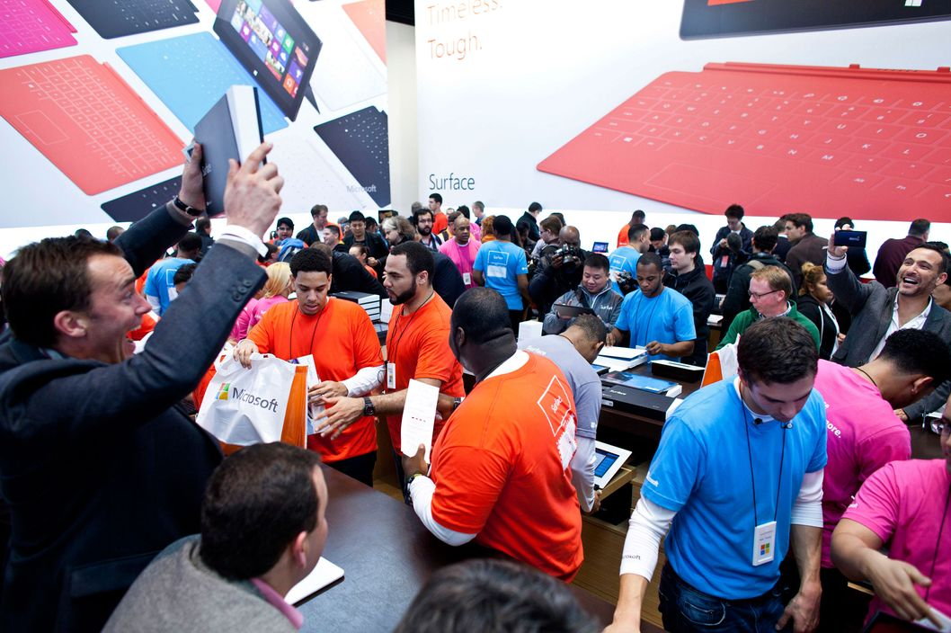 Customers purchase Microsoft Corp. Surface tablets inside the company's store during its grand opening in New York, U.S., on Thursday, Oct. 25, 2012. Microsoft Corp. introduced the biggest overhaul of its flagship Windows software in two decades, reflecting the rising stakes in its competition with Apple Inc. and Google Inc. for the loyalty of customers who are shunning personal computers and flocking to mobile devices. Photographer: Ramin Talaie/Bloomberg via Getty Images