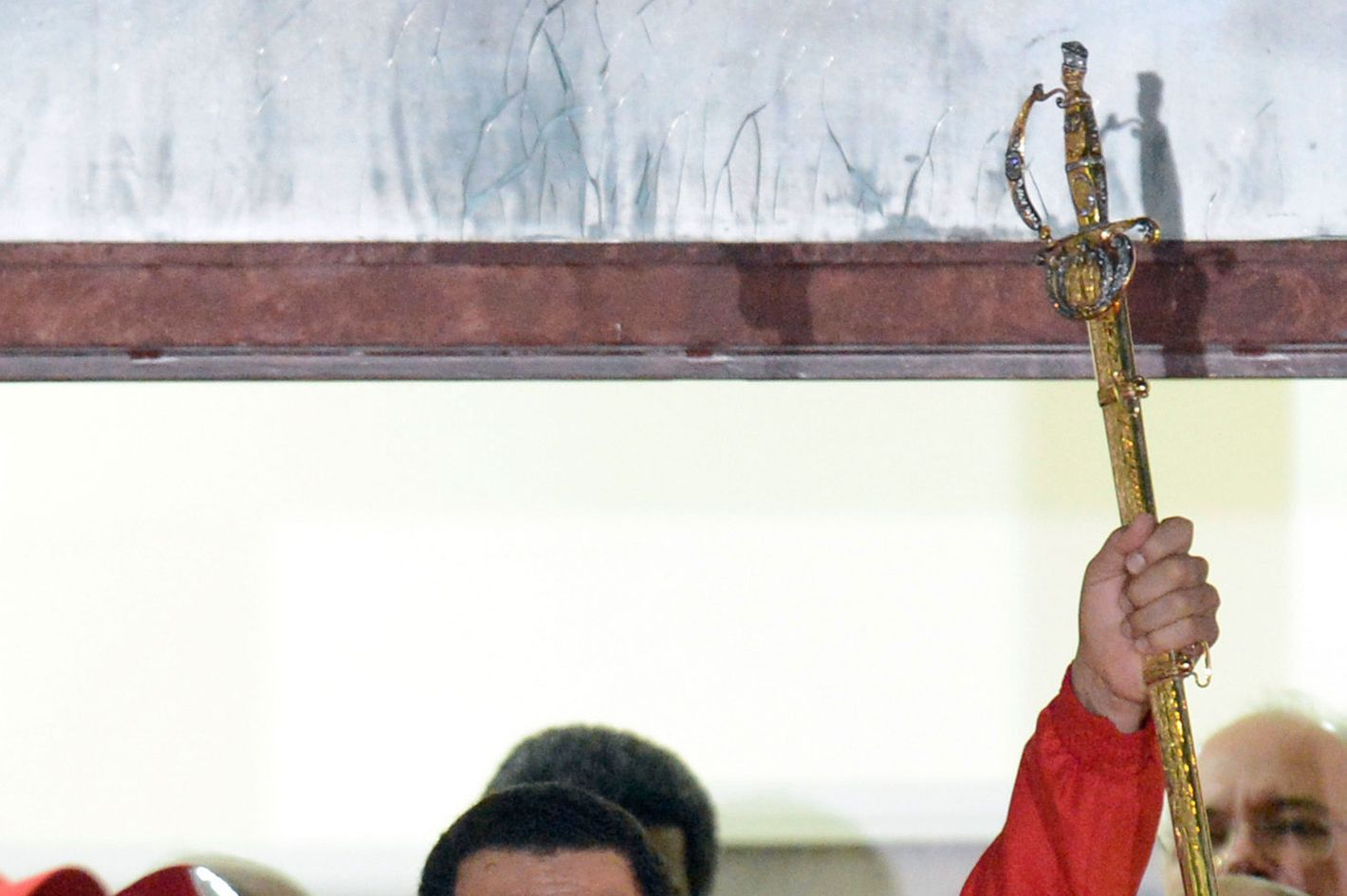 Venezuelan President Hugo Chavez (C) holds the sword of South American liberator Simon Bolivar while speaking to supporters after receiving news of his reelection in Caracas on October 7, 2012. According to the National Electoral Council, Chavez was reelected with 54.42% of the votes, beating opposition candidate Henrique Capriles, who obtained 44.47%. AFP PHOTO/JUAN BARRETO