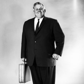 A portly gentleman in a business suit, carrying an attache case and smiling broadly.