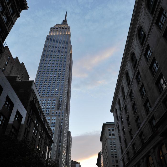 Past the Empire State Building (L), the sun sets along 34th Street aligning with the Manhattan street grid during
