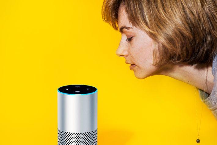 A woman leans toward an Amazon Echo device.