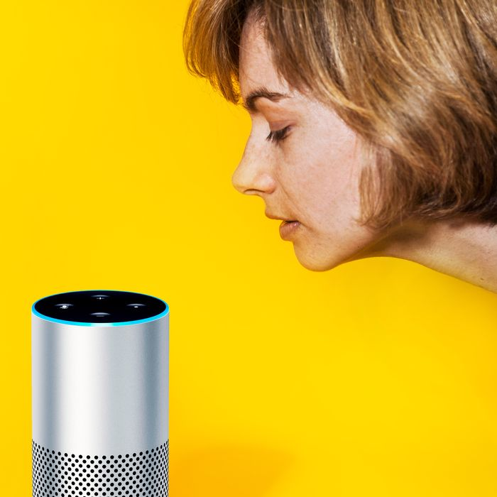 A woman leans toward an Amazon Echo device.