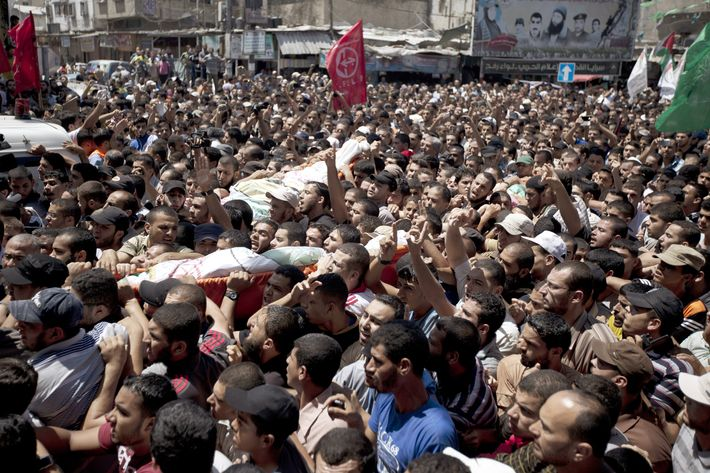 Palestinian mourners carry the bodies of three senior Hamas commanders during their funeral in the southern Gaza Strip town of Rafah on August 21,2014. Israeli warplanes killed three top Hamas commanders in southern Gaza inflicting a heavy blow on the movement's armed wing after failing to kill its top military chief. AFP PHOTO / MAHMUD HAMS        (Photo credit should read MAHMUD HAMS/AFP/Getty Images)