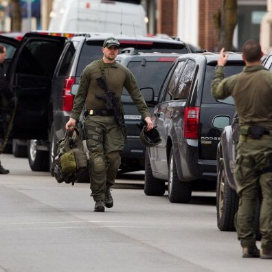 HERKIMER, NY - MARCH 13: Tactical police officers return to their vehicles on North Main Street, equipment in hand, after waiting at the scene of a standoff with a murder suspect on March 13, 2013 in Herkimer, New York. Police have identified 64-year-old Kurt Meyers as a possible suspect responsible for a total of four shooting deaths and two injuries across the area earlier in the day. (Photo by Brett Carlsen/Getty Images)