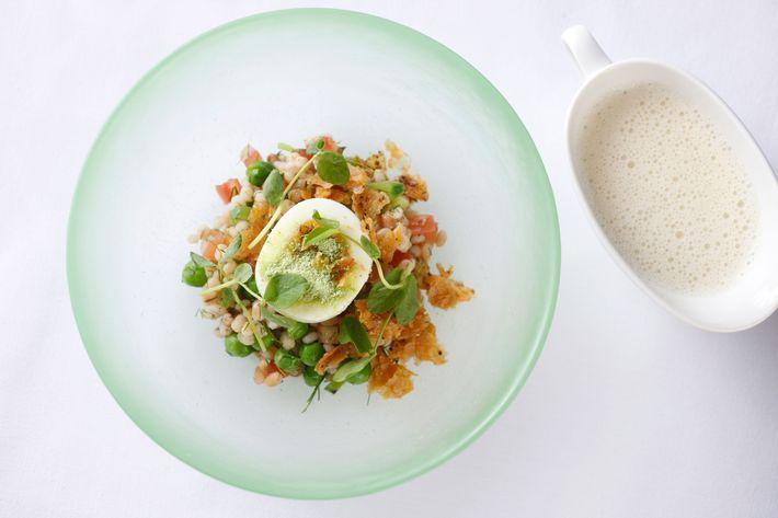 Soft-boiled egg, chicken cracklings, sugar snap peas, and barley.