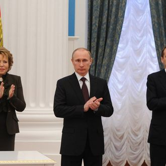 MOSCOW, RUSSIA - MARCH 21: Sergey Naryshkin (R) Chairman of the State Duma and Valentina Matviyenko (L) the Chairwoman of the Federation Council of the Russian Federation stand next to the Russian President Vladimir Putin as he signs set of laws on reunification of Crimea, Sevastopol with Russia at Ekaterininsky in Kremlin, March 21, 2014.