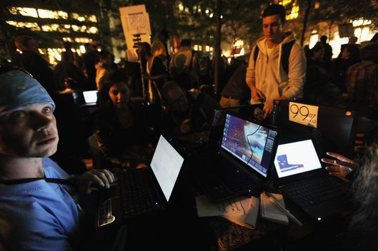 NEW YORK, NY - OCTOBER 05:   Protesters affiliated with the Occupy Wall Street movement work on their laptops to upload images and videos after a march on October 5, 2011 in New York City. Thousands of protesters including union members and college students from an organized walkout joined today's rally and march. (Photo by Mario Tama/Getty Images)