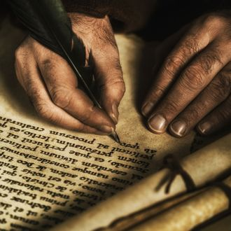 Hands writing on parchment