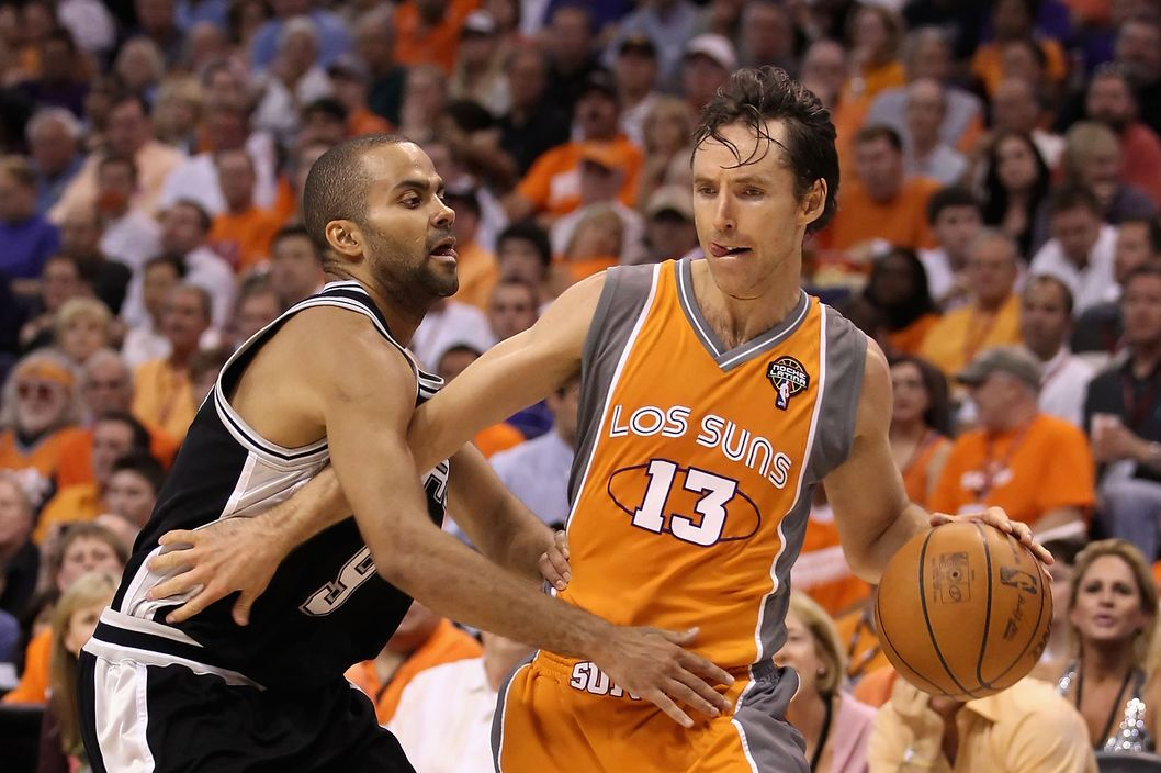 "PHOENIX - MAY 05:  Steve Nash #13 of the Phoenix Suns handles the ball under pressure from Tony Parker #9 of the San Antonio Spurs during Game Two of the Western Conference Semifinals of the 2010 NBA Playoffs at US Airways Center on May 5, 2010 in Phoenix, Arizona. The team is wearing ""Los Suns"" jerseys on Cinco de Mayo in response to an anti-immigration law recently passed in Arizona.  The Suns defeated the Spurs 110-102 to take a 2-0 series lead.  NOTE TO USER: User expressly acknowledges and agrees that, by downloading and or using this photograph, User is consenting to the terms and conditions of the Getty Images License Agreement.  (Photo by Christian Petersen/Getty Images) *** Local Caption *** Steve Nash;Tony Parker"