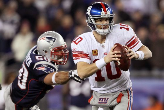 FOXBORO, MA - NOVEMBER 06:  Eli Manning #10 of the New York Giants scrambles as Rob Ninkovich #50 of the New England Patriots defends on November 6, 2011 at Gillette Stadium in Foxboro, Massachusetts. The New York Giants defeated the New England Patriots 24-20.  (Photo by Elsa/Getty Images)