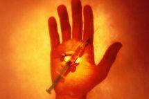 Hand Holding Pills and Syringe