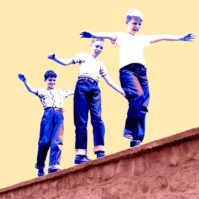 1950s Laughing Boys Walking On Top Of Stone Wall Arms Out Balancing Playing Follow The Leader.