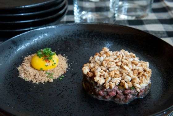 Beef tartare: black trumpet mushrooms, puffed farro, anchovy, and egg yolk.