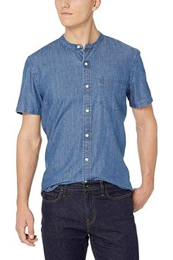 A male model wearing a blue denim standard fit band collar button-down shirt with a breast pocket from Goodthreads with dark wash jeans. The Strategist - A Bunch of Men's Button Downs (From $16) Are on Sale at Amazon.